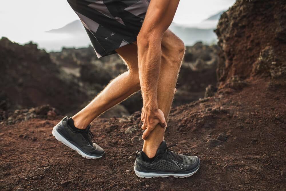 Male runner holding injured calf muscle and suffering