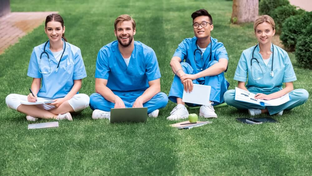 Multicultural medical students sitting on grass