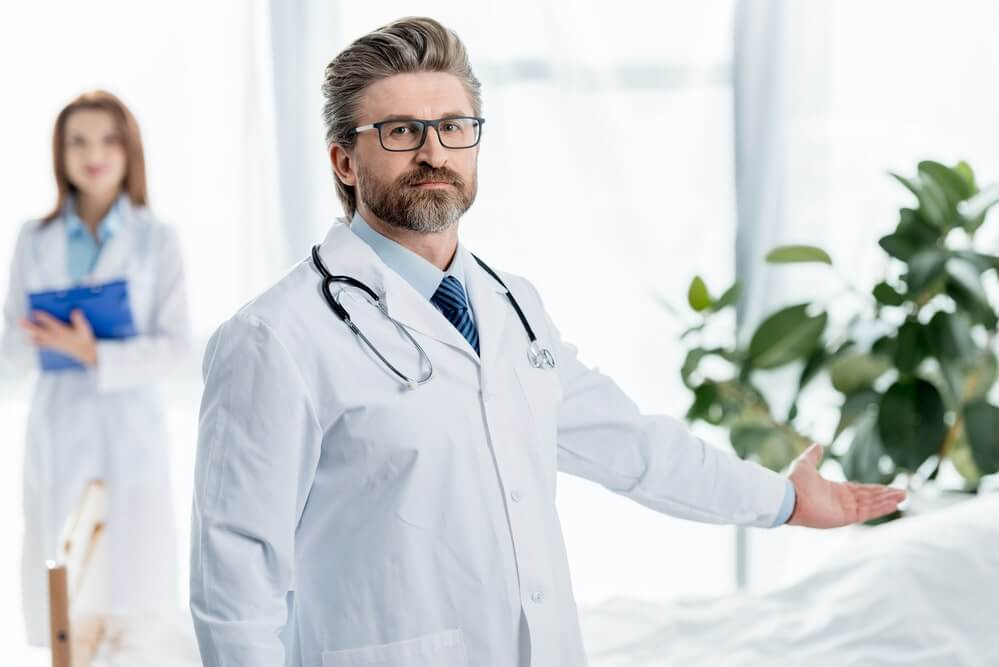 Selective focus of doctor in white coat pointing