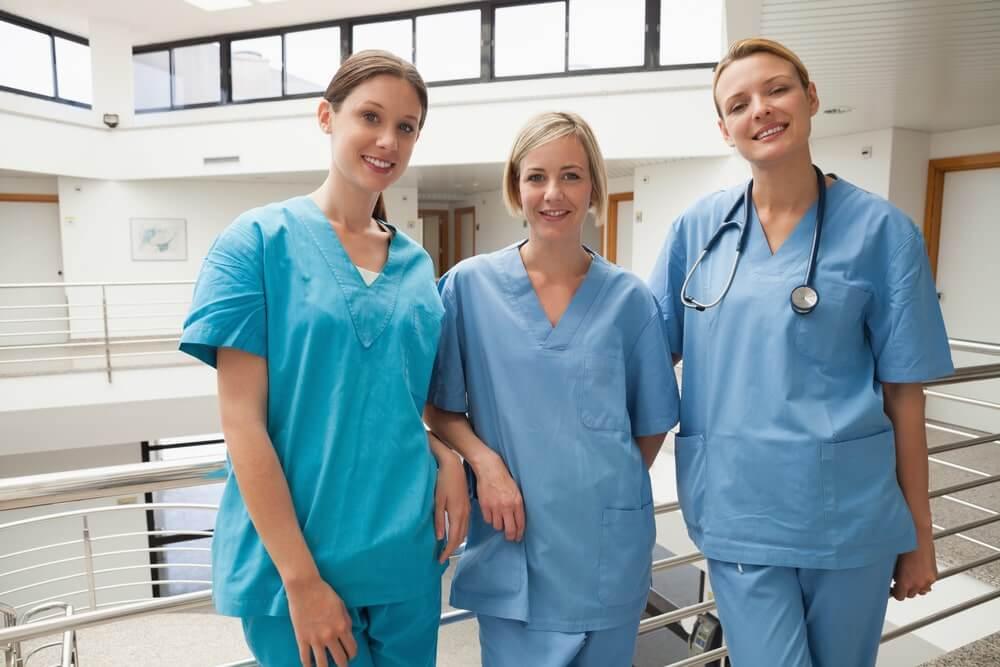 Three nurses leaning against railing