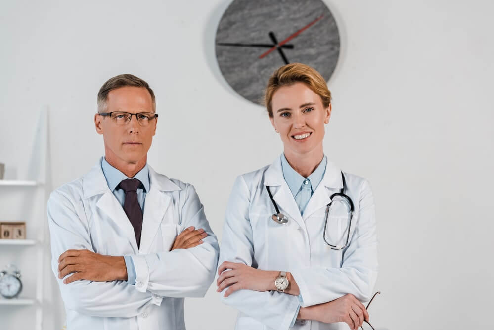 Handsome doctor standing with crossed arms