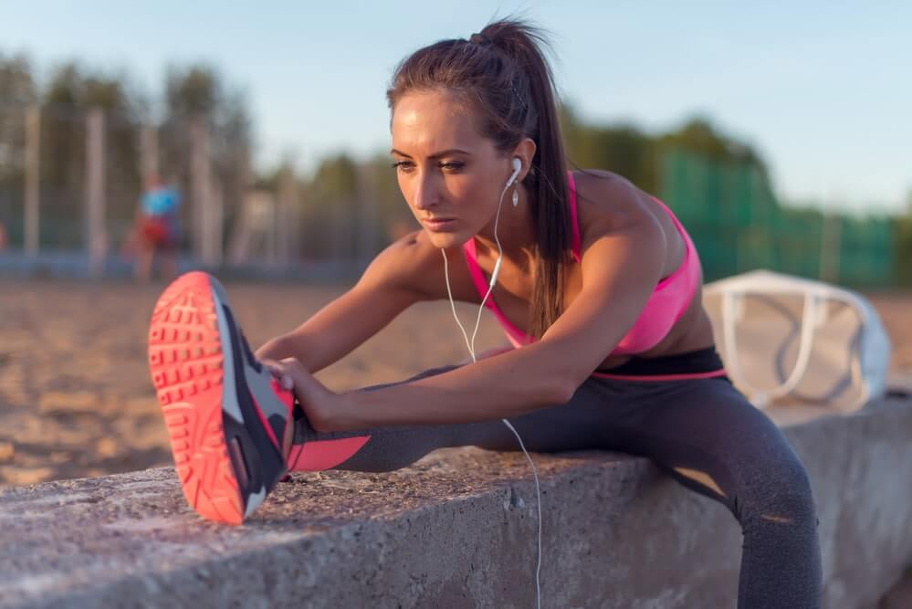 Fitness model athlete girl warm up stretching her hamstrings, leg and back. Young woman exercising with headphones listening music outdoors on beach or sports ground at evening summer
